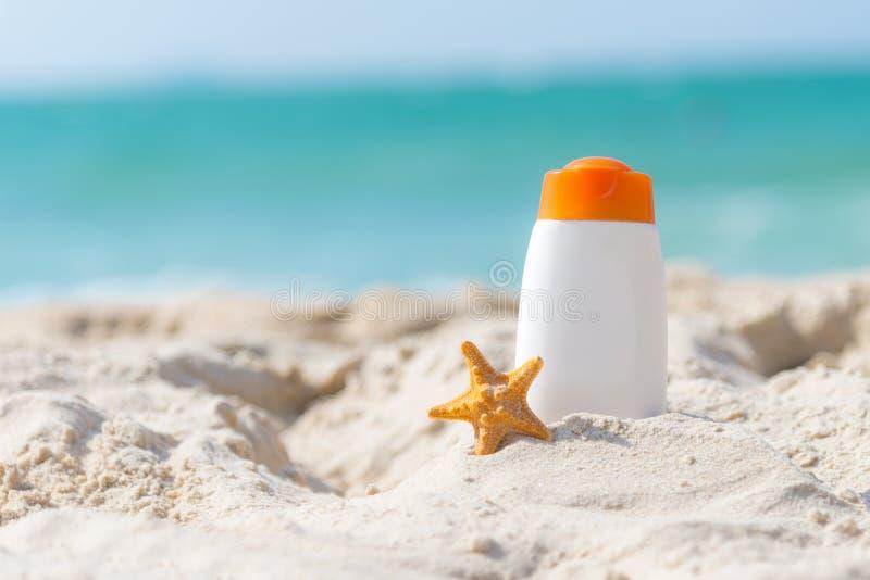 Skyddande sunscreen- eller sunblock- och sunbathlotion i vita plast- flaskor med sandaler på den tropiska stranden, sommartillbeh royaltyfria bilder