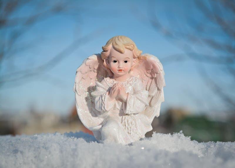 Skyddsängel på bakgrund för blå himmel Religion- och trobegrepp vinter för blommasnowtid royaltyfria bilder