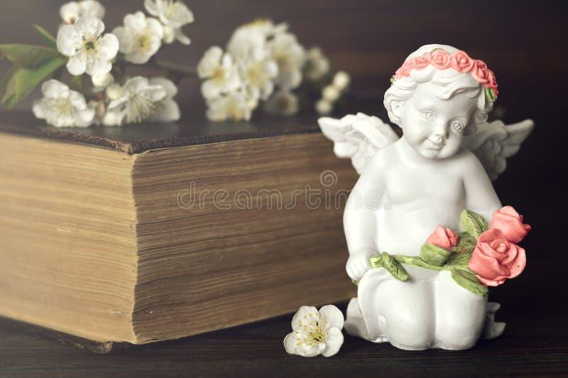 Skyddsängel som knäfaller och rymmer blommor arkivfoto