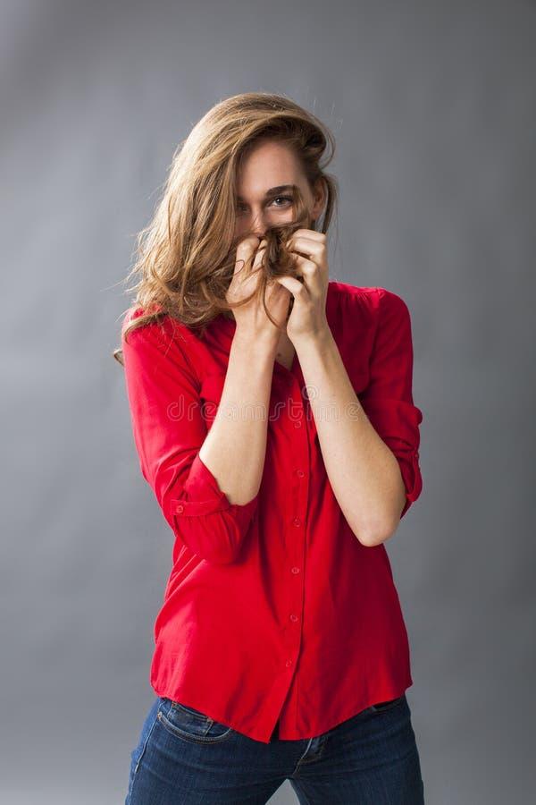 Skyddsbegrepp för den förtjusande unga kvinnan som spelar med hennes hår arkivfoto