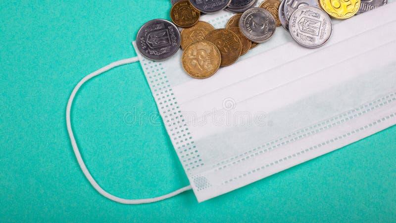 Skyddsmask och en handfull mynt på blå bakgrund stigande läkemedelspriser på grund av den pandemiska coronavirus covid-19 arkivfoton