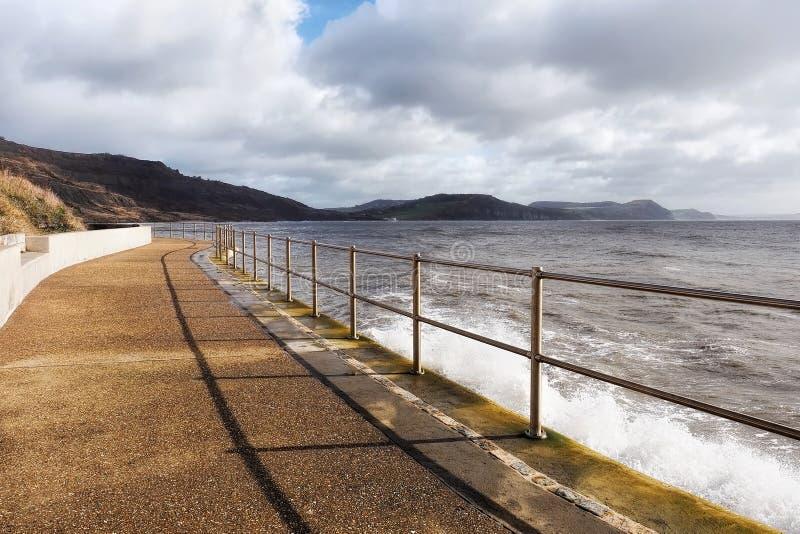 Skyddsmur mot havet längs den tillbaka stranden - Lyme Regis royaltyfri bild