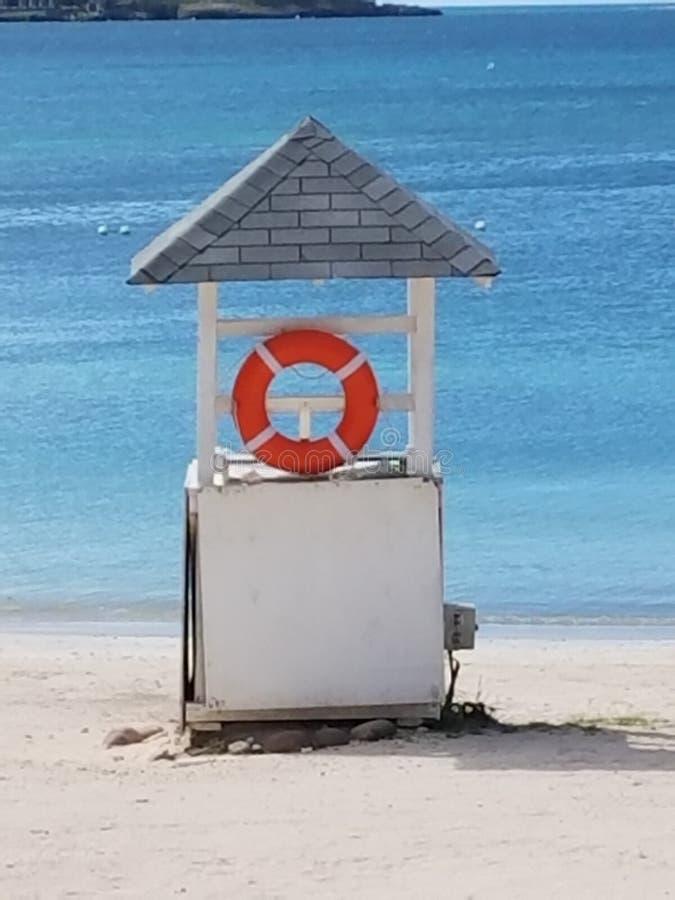 Skyddspost på en strand som är vänd mot blått hav arkivbild