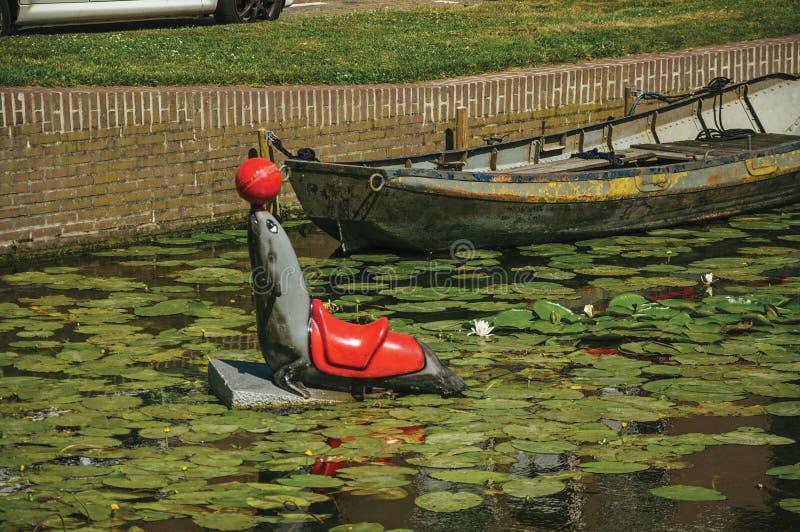 Skyddsremsastaty med bollen i näsan på kanalvattnet med vatten- växter på Weesp arkivbild
