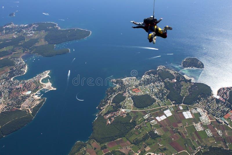 Skydive em tandem na queda livre sobre o mar azul imagens de stock royalty free