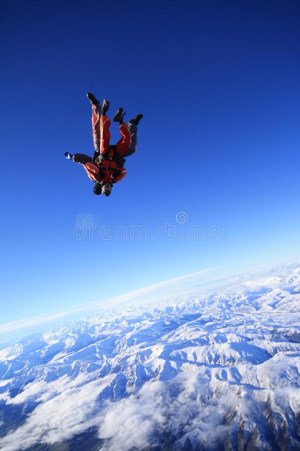 Skydive over snow mountain stock images