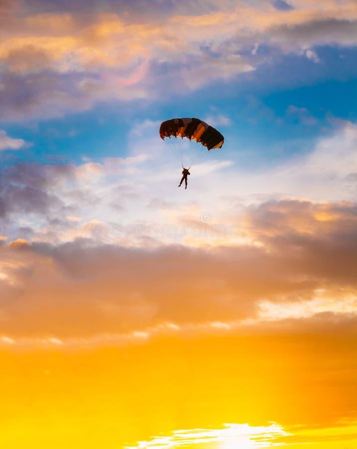 Skydiver auf buntem Fallschirm in Sunny Sunset lizenzfreie stockfotos