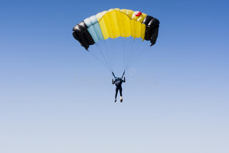 Skydiver in clean sky with copy space. Yellow parachute royalty free stock photos