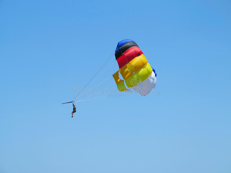 Skydiver del paracaidista en backgrou del paracaídas colorido y del cielo azul fotos de archivo libres de regalías