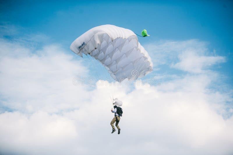Skydiver die op wit valscherm in blauwe duidelijke hemel bij een heldere zonnige de zomerdag vliegen Actieve Levensstijl, Extreme stock fotografie
