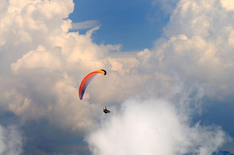 Skydiver flies over the mountains. Extreme recreation, skydiver flies over the mountains and rocks. White clouds in sky royalty free stock image