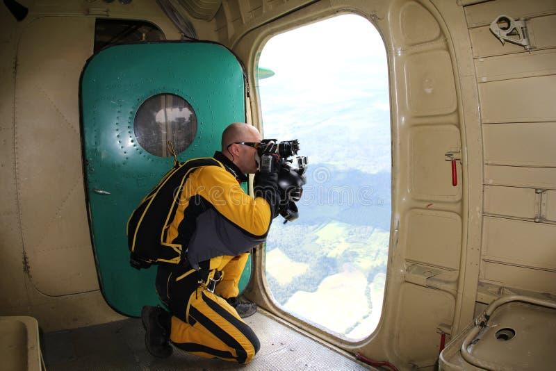 Skydiver maakt film van geopende deur van een vliegtuig stock afbeelding