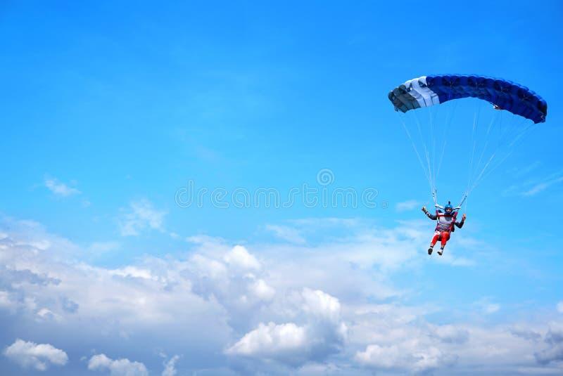 Skydiver met een donkerblauwe luifel op de achtergrond een blauwe hemel boven wolken, close-up stock foto's