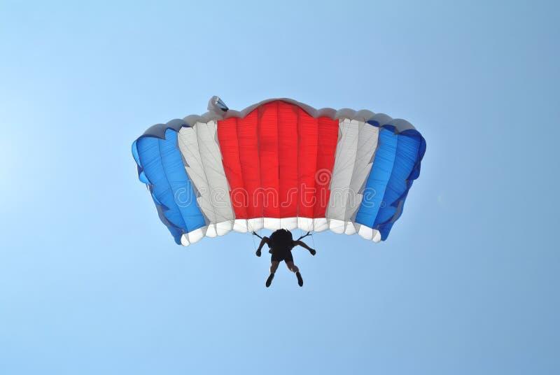 Skydiver met het blauwe witte rode valscherm skydiving stock fotografie
