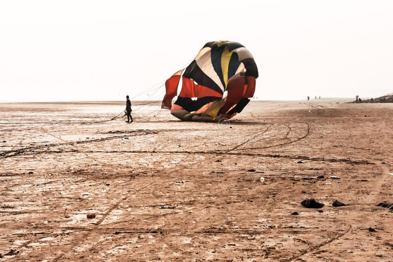 Skydiver with orange and yellow parachute runs after landing in Dona Paula Beach, near Colva and Vagator Beach Goa against sky and royalty free stock image
