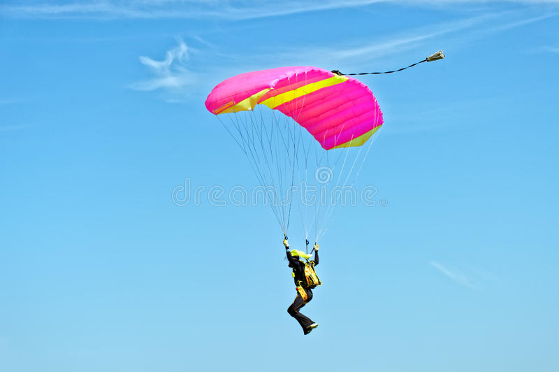 Skydiver on parachute. Paraglider flying on colorful parachute in blue clear sky at a bright sunny summer day. Active lifestyle, extreme hobbies royalty free stock photos