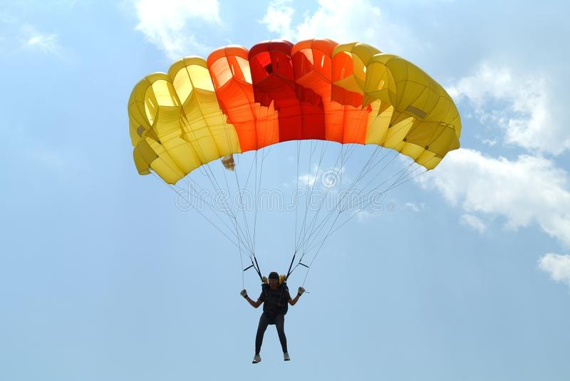 Skydiver skydiving with colourful yellow orange red parachute on St. Peter`s Parachuting Cup. Held in city Prijedor, RS, Bosnia & Herzegovina in 2016 stock image