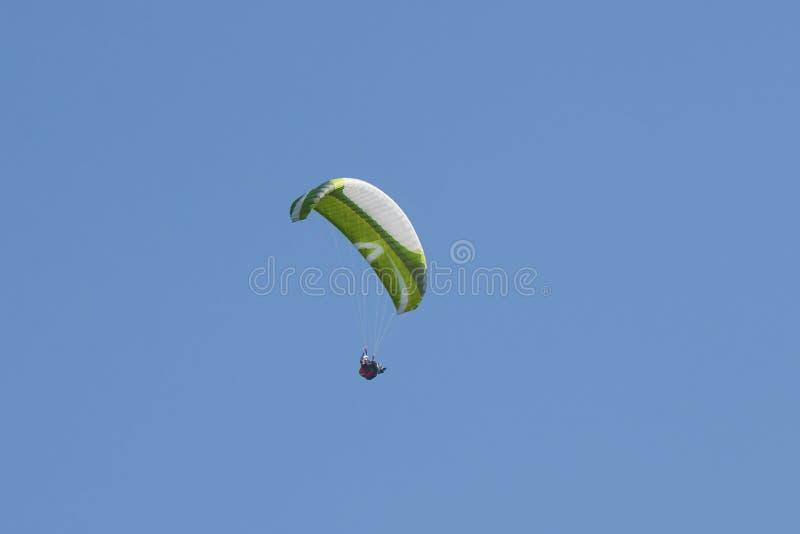 Skydiver verde que vuela con el cielo azul en el fondo foto de archivo libre de regalías