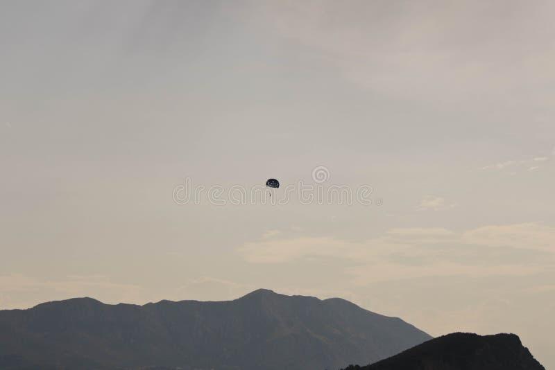 Skydiver vliegt ver in de hemel over de bergen royalty-vrije stock foto