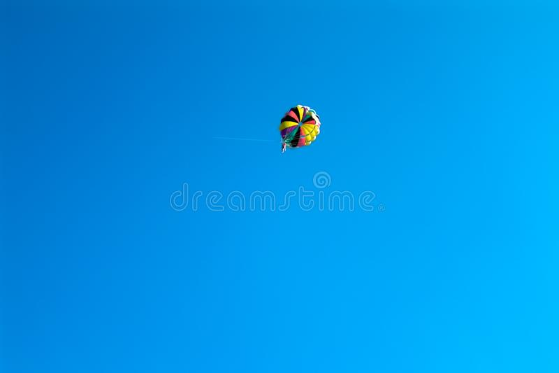 Skydiverfliegen auf farbigem Fallschirm im blauen klaren Himmel stockbilder