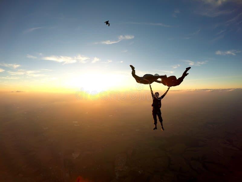 Skydivers die pret hebben bij de zonsondergang stock fotografie