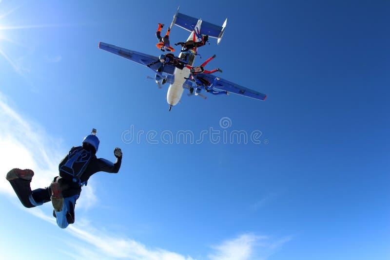 Skydivers leidt en springt uit een vliegtuig op royalty-vrije stock foto's