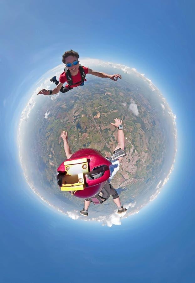 Skydivers que têm a opinião pequena do planeta do divertimento foto de stock