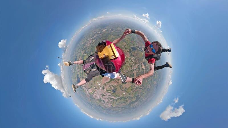 Skydivers que têm a opinião pequena do planeta do divertimento fotografia de stock royalty free
