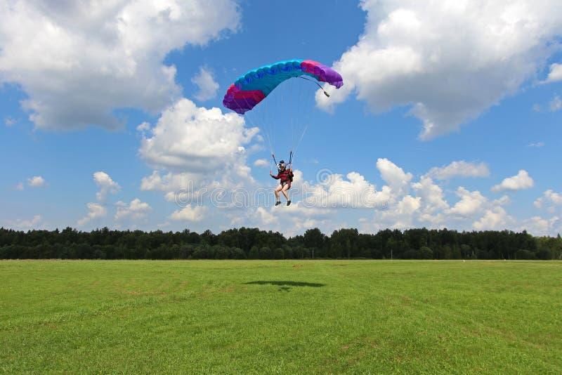 skydiving Девушка приземляется на зеленое поле стоковые изображения