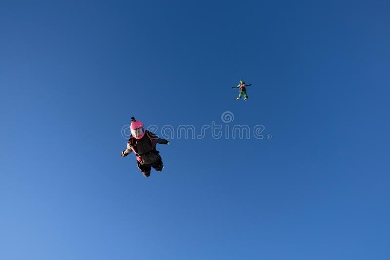 skydiving 两个女孩在天空蔚蓝飞行 免版税库存图片