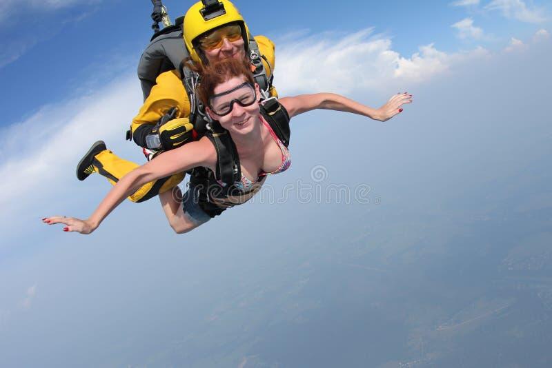 skydiving 女孩和辅导员在天空飞行 免版税库存照片