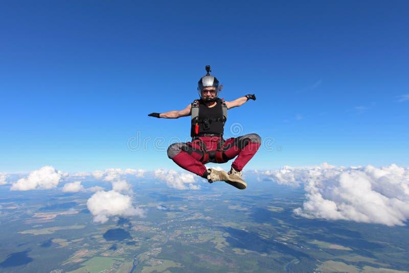 skydiving 愉快的女孩在瑜伽位置跌倒 库存照片