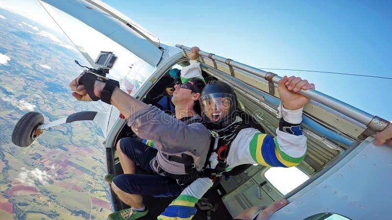 Skydiving achter elkaar bij de deur van het vliegtuig stock foto