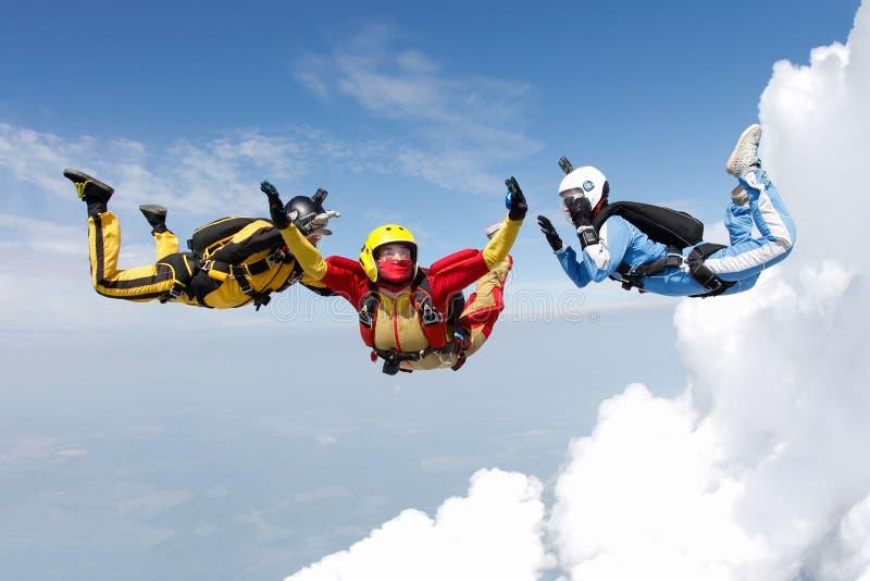 skydiving Deux instructeurs forment un étudiant pour voler image stock
