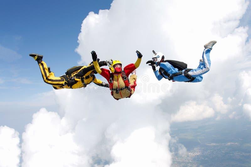 skydiving Deux instructeurs forment un étudiant pour voler photos stock