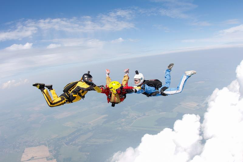 skydiving Deux instructeurs forment un étudiant pour voler photo libre de droits
