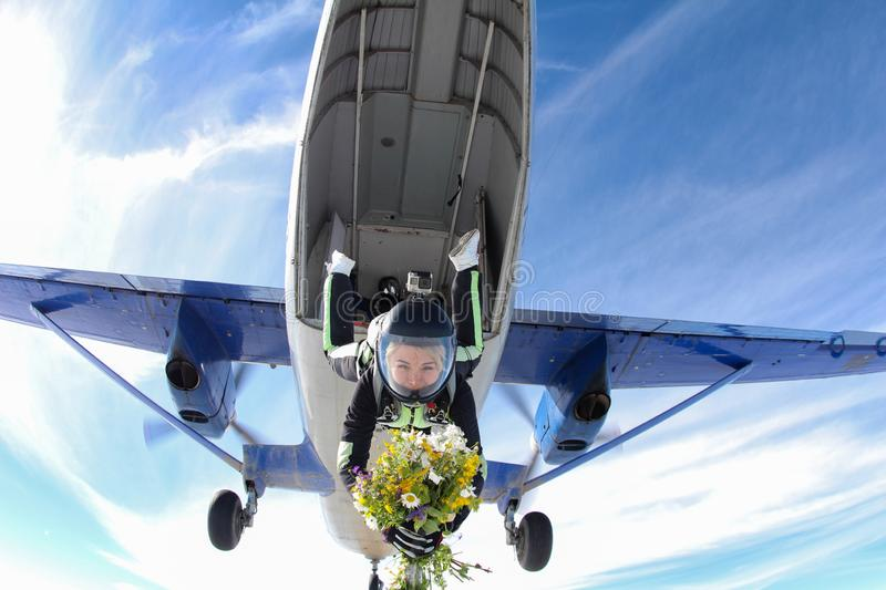 Skydiving. Girl with flowers is jumping out of a plane. stock photos