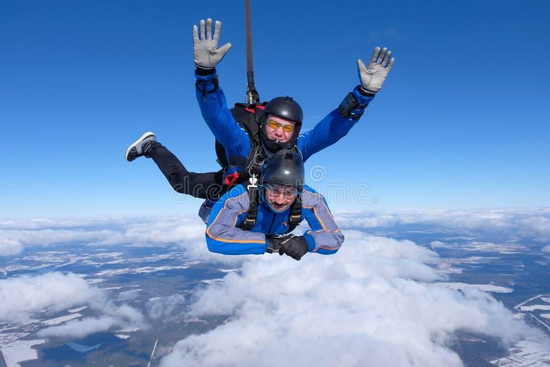 Skydiving het achter elkaar Twee kerels zijn in de blauwe hemel stock afbeeldingen