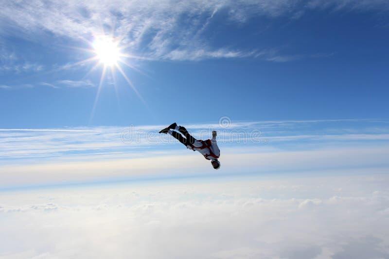 skydiving Le parachutiste vole au-dessus des nuages blancs photos stock