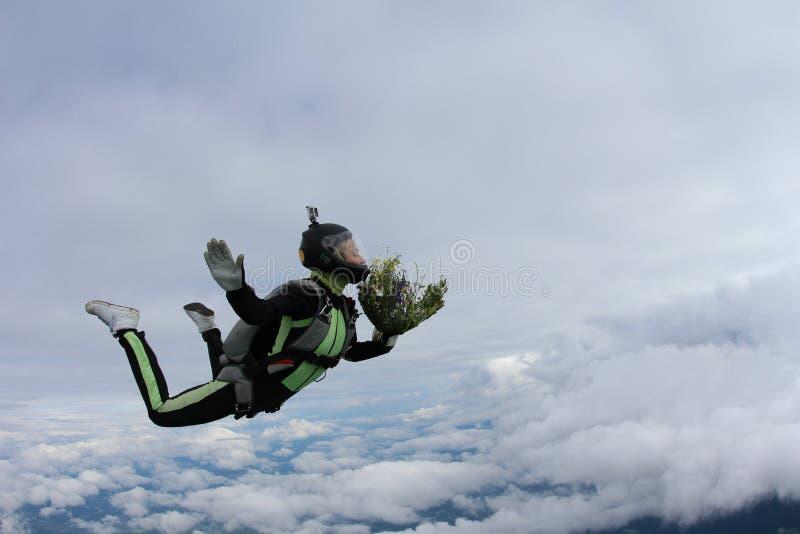 skydiving Mädchen mit Blumenstrauß im Himmel lizenzfreies stockfoto