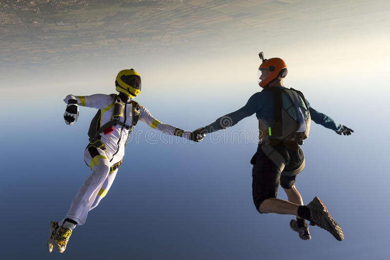 Skydiving photo. Boy and girl parachutist in free style stock image