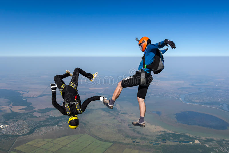 Skydiving photo. A girl and a guy skydivers perform pieces in free fall royalty free stock photo