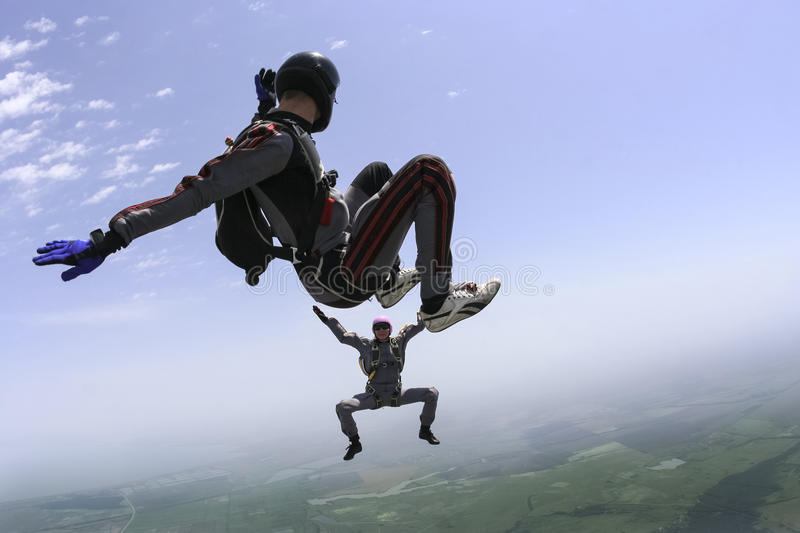 Skydiving photo. A girl and a guy skydivers perform pieces in free fall royalty free stock image