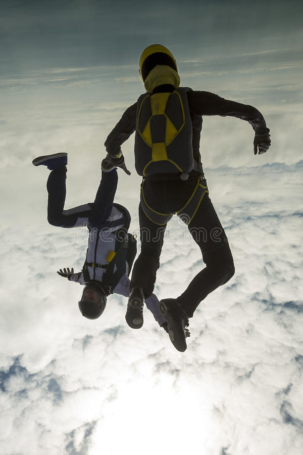 Skydiving photo. A girl and a guy skydivers perform pieces in free fall royalty free stock images