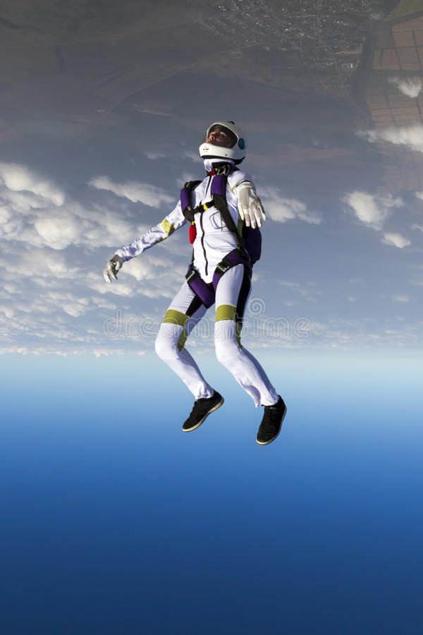 Skydiving photo. The girl parachutist performs figure freestyle in freefall royalty free stock image