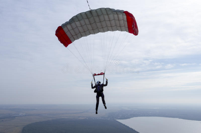 Skydiving photo. The girl parachutist pilots his parachute stock photography