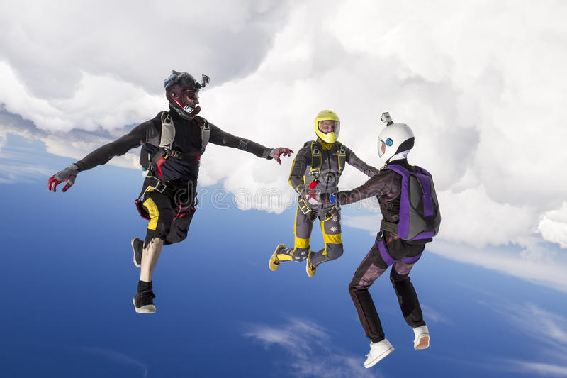 Skydiving photo. Three parachutists perform freestyle figures in free fall royalty free stock photo