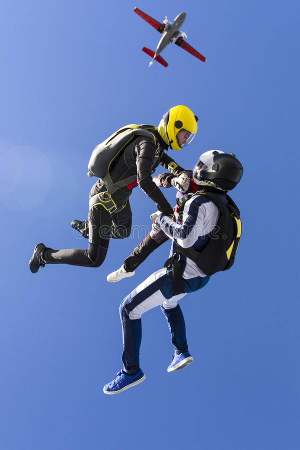 Skydiving photo. Two girls and a guy skydivers jump out of an airplane stock photos