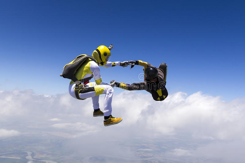 Skydiving photo. Two sports parachutist build a figure in free fall royalty free stock photo