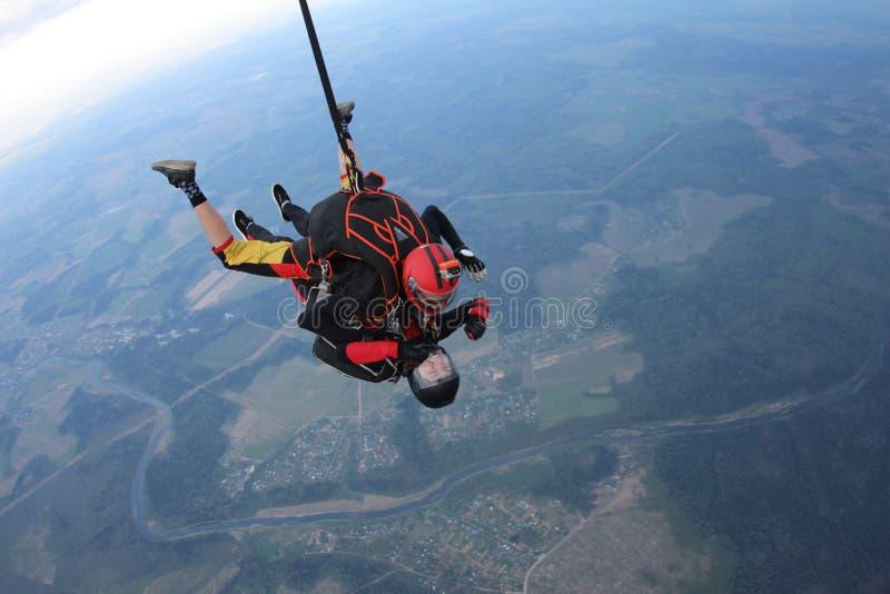 skydiving Salto em tandem O homem e a jovem mulher estão caindo no céu junto fotografia de stock royalty free